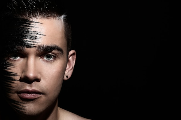 Handsome guy with artistic black shadow on his face
