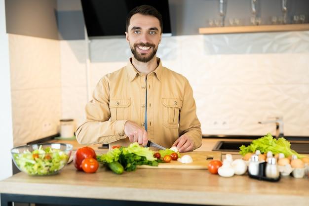Красивый парень с бородой и красивой улыбкой готовит салат. он, наверное, любит здоровый образ жизни