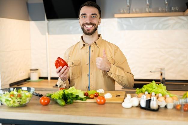 Красивый парень с бородой и красивой улыбкой дает понять, что такое здоровый образ жизни и есть свежие продукты.