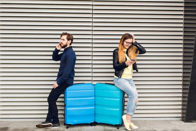 Bel ragazzo con la barba appoggiato sulla valigia su sfondo grigio a strisce e parlando al telefono. bella ragazza con i capelli lunghi in bicchieri vicino appoggiato anche sulla valigia e sta scrivendo sul telefono.