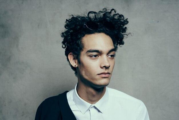 灰色の背景の写真スタジオの肖像画に白いシャツとジャケットの巻き毛を持つハンサムな男
