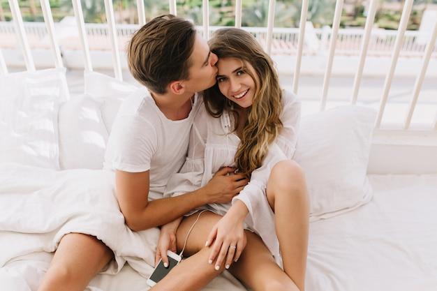 朝のベッドの上に座って額に彼の魅力的な女の子に優しくキスする黒髪のハンサムな男。ソファで横になっていると週末に一緒に時間を過ごす怠惰なかわいい若いカップル