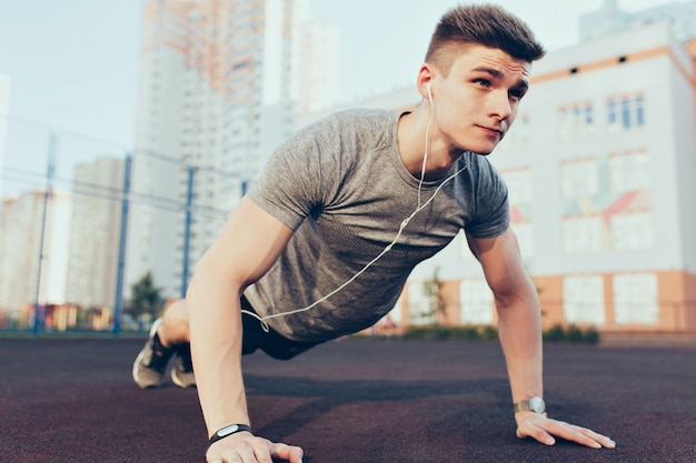 Handsome guy with a good body push-ups in the morning on stadium. he wears sport clothes, listening to music through headphones. he looks tense.