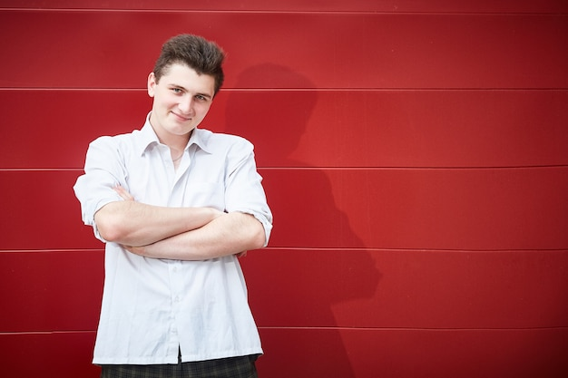 A handsome guy with his arms folded across his chest stands near a red wall.