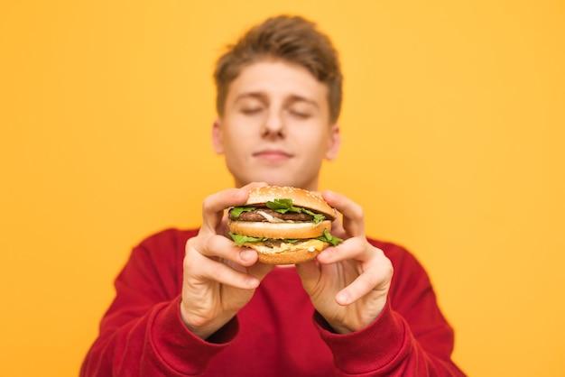 目を閉じてハンサムな男がカメラにおいしい大きなハンバーガーを示しています