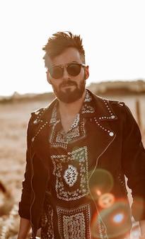 Красивый парень с кожаной курткой и солнцезащитными очками