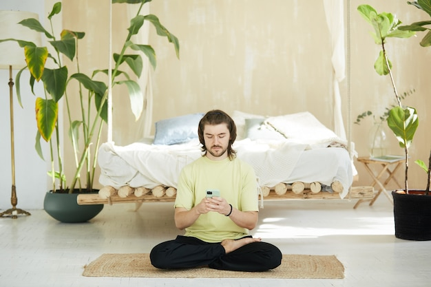 Handsome guy with long hair using phone sitting on floor, yoga teacher typing on smartphone at home on the yoga mat