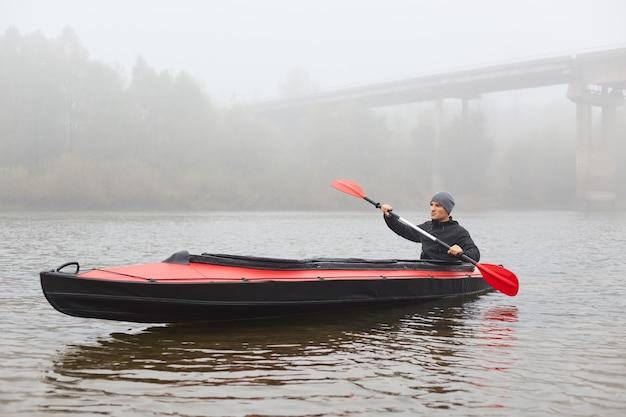 Красивый парень с веслом в руках гребет на лодке и смотрит вдаль