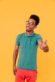 Handsome guy with pleased face expression standing. indoor shot of joyful brunette african man in big glasses.