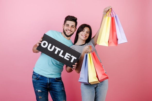 Handsome guy with pretty brunette girl with outlet sign and colorful shopping bags