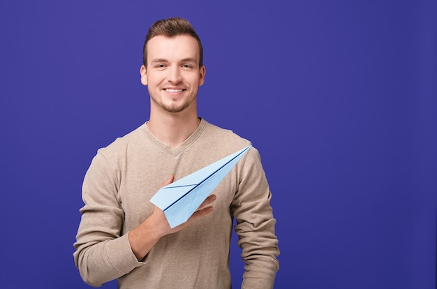 Handsome guy with smile holds paper plane.