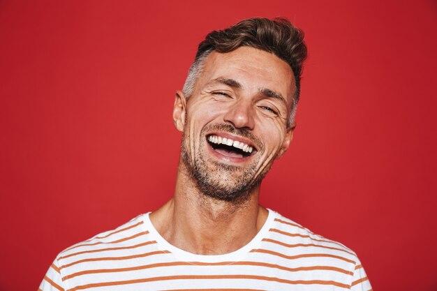Красивый парень с щетиной в полосатой футболке смеется изолированно на красном