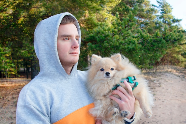 Handsome guy, young man in hood hugging, walking with pomeranian spitz dog. boy with beautiful cute furry puppy on hands outdoors in park or forest. people love their pet, animals concept.