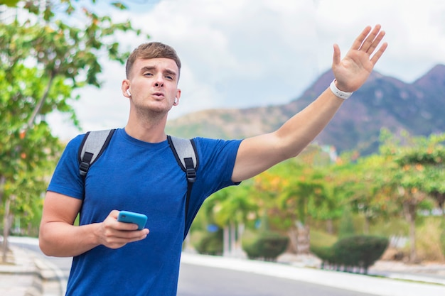 Handsome guy, young man in hurry late, trying to stop, catch a taxi car or cab. boy standing near road with backpack and cell mobile phone, raise, waving his hand, holding arm up. hitchhiker