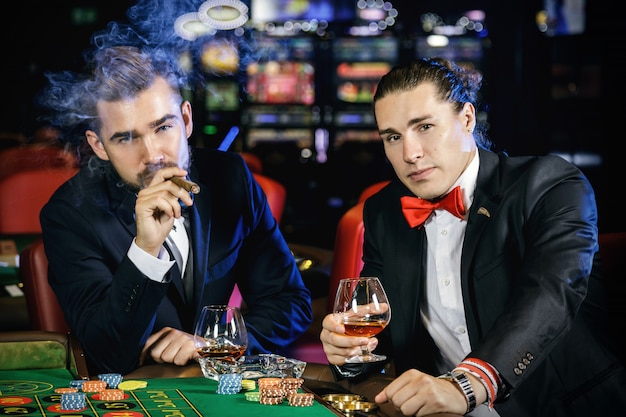 Handsome guys drinking cognac and playing roulette in the casino