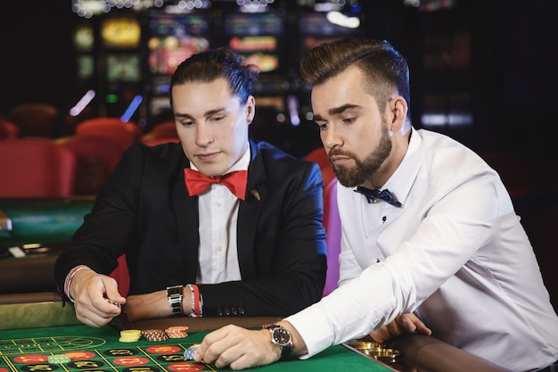 Handsome guys playing roulette in the casino