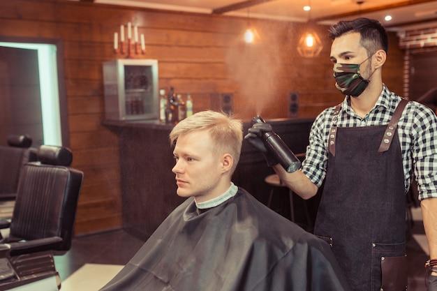 男性のクライアントの髪を切るハンサムな美容師。ヴィンテージ理髪店でクライアントにサービスを提供する男性のヘアスタイリスト。 Premium写真