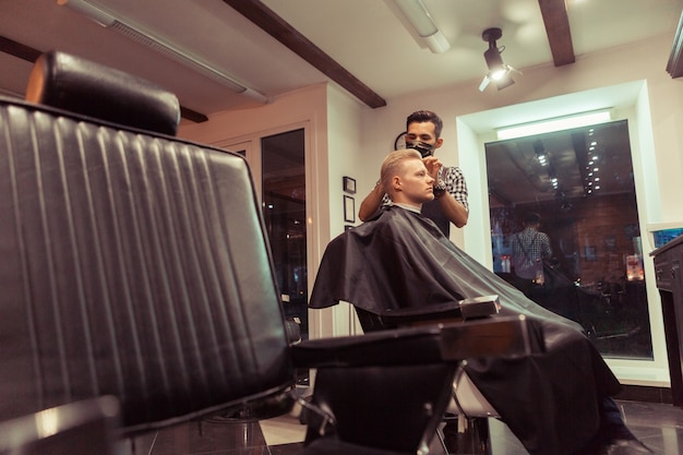 男性のクライアントの髪を切るハンサムな美容師。ヴィンテージ理髪店でクライアントにサービスを提供する男性のヘアスタイリスト。