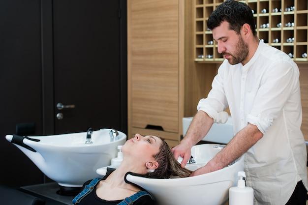 ハンサムな美容師が集中して女性の髪を洗います。彼は水栓を持っています。シンクに頭をもたれて女性。
