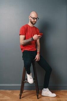 Красивый лысый мужчина с бородой, очками, красной футболкой разговаривает по телефону, текстовые сообщения, держа смартфон