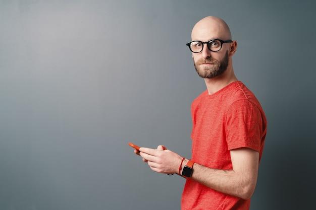Красивый лысый мужчина с бородой, очками, красной футболкой, текстовыми сообщениями, держа смартфон