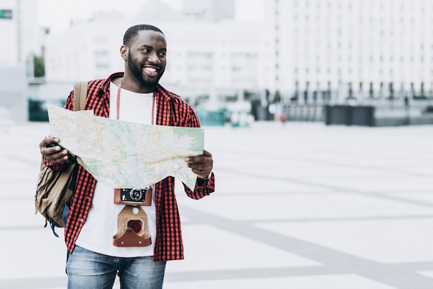 Handsome and happy afro american tourist with old camera and map in modern city