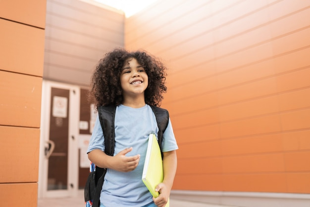 Handsome happy afro boy leaves school, back to school, backpack and notebook, preschool