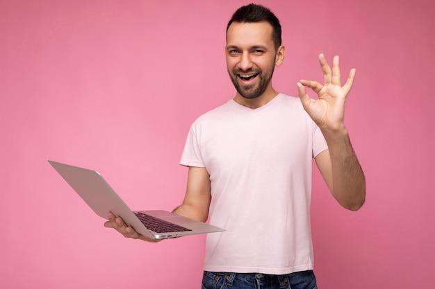 Красивый счастливый и смешной брюнет человек, держащий портативный компьютер и показывающий жест, нормально глядя на камеру в футболке на изолированном розовом фоне.