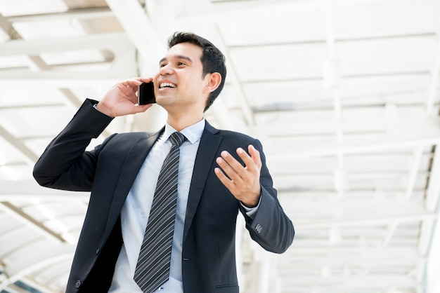 Handsome happy asian businessman talking to client on mobile phone in the city