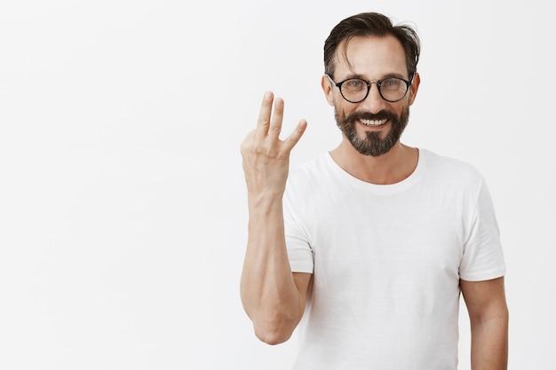 Красивый счастливый бородатый зрелый мужчина в очках позирует