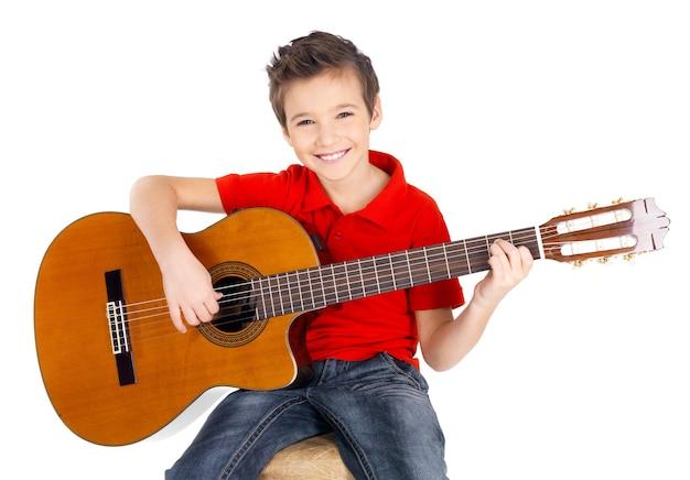 ハンサムな幸せな少年は白で隔離のアコースティックギターで遊んでいます