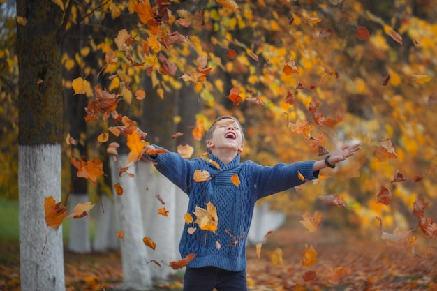 Handsome happy boy throwing the fallen leaves up, playing in the autumn park.