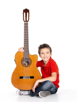 Handsome happy boy with the acoustic guitar- isolated on white background