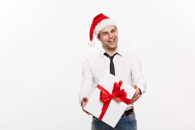 Handsome happy business man giving gift with wear santa hat posing