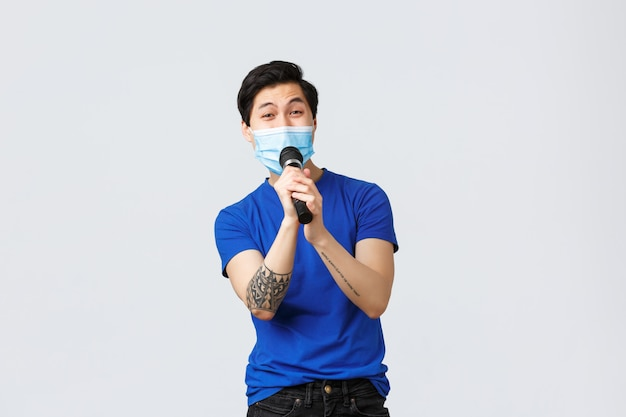 Handsome happy and carefree chinese guy having fun at karaoke, singing song in microphone, wearing medical mask
