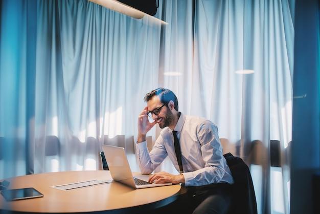 シャツとネクタイと眼鏡のオフィスに座っていると重要なプロジェクトに取り組んでいるハンサムな幸せな白人実業家。企業のビジネスコンセプトです。