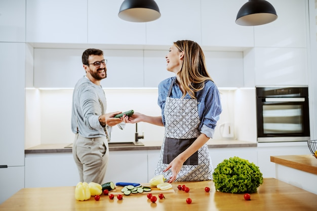 Handsome happy caucasian couple standing in kitchen and preparing healthy meal. man giving woman fresh cucumber that he washed. on kitchen counter are all sorts of vegetables.