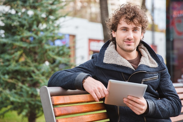 Handsome happy cheerful attractive content young man sitting on wooden bench in park and holding tablet