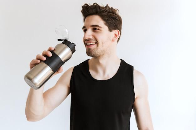Красивый счастливый жизнерадостный молодой сильный спортивный мужчина позирует и питьевой водой.