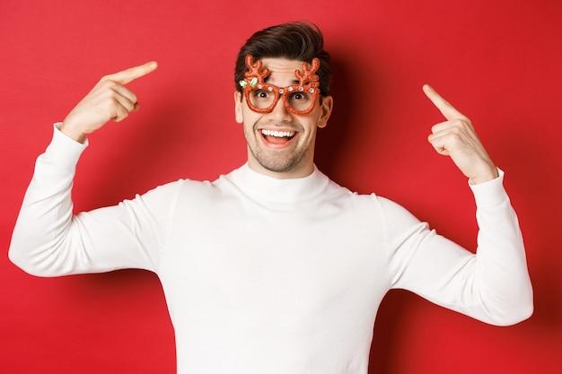 白いセーターを着たハンサムな幸せな男、彼のクリスマスパーティーのメガネを指して、新年を祝って楽しんで、赤い背景の上に立って