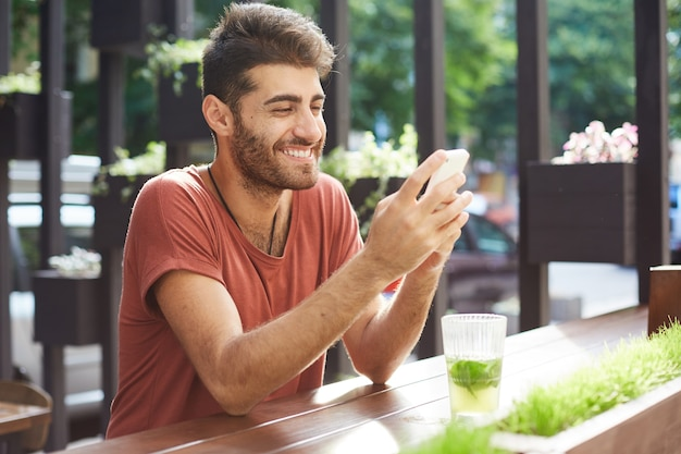 Handsome happy guy sitting in cafe, drinking lemonade and using mobile phone, texting message