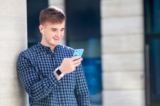 ワイヤレスbluetoothイヤホンairpodsと電話でメッセージを入力して笑っているハンサムな幸せな男。ガジェット、デバイス、ソーシャルメディアのコンセプト