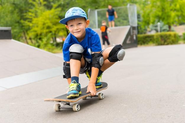 スケートボードに乗ったハンサムな幸せな少年がしゃがんでボード上でバランスを取りながらカメラに向かって幸せそうに笑う