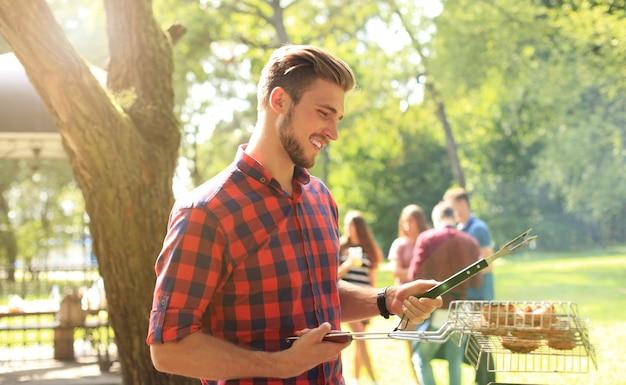 야외에서 친구들을 위해 바베큐를 준비하는 잘생긴 행복한 남성.