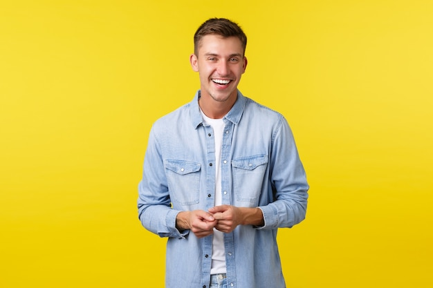 Handsome happy male student in casual outfit, laughing and smiling, having lively conversation. man looking joyfully camera, standing yellow background, talking to friend.