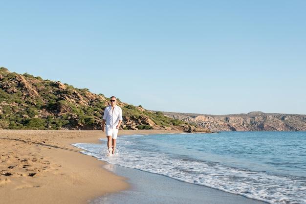 ビーチを歩いている白いシャツのハンサムな幸せな男。