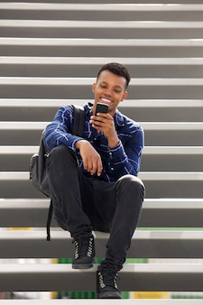 Handsome happy man sitting on steps using smart phone