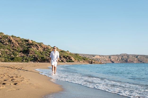 Handsome happy man in white shirt walking on the beach.