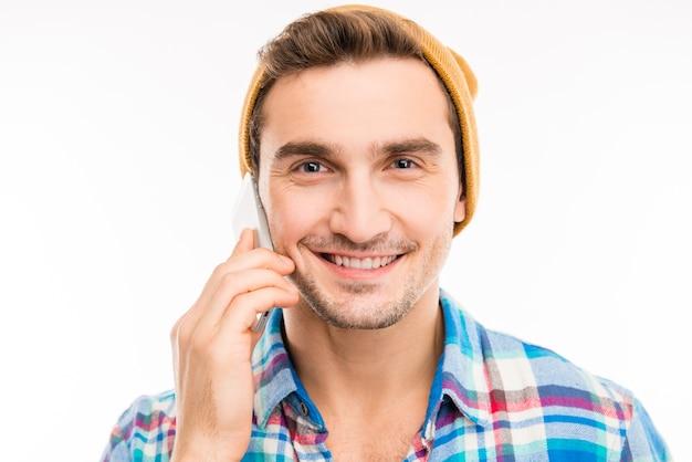 電話で話している帽子とハンサムな幸せな男
