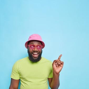 Bell'uomo felice con punti di barba folta nell'angolo in alto a destra vestito con abiti estivi occhiali da sole rosa alla moda mostra lo spazio della copia per la tua pubblicità isolata sulla parete blu